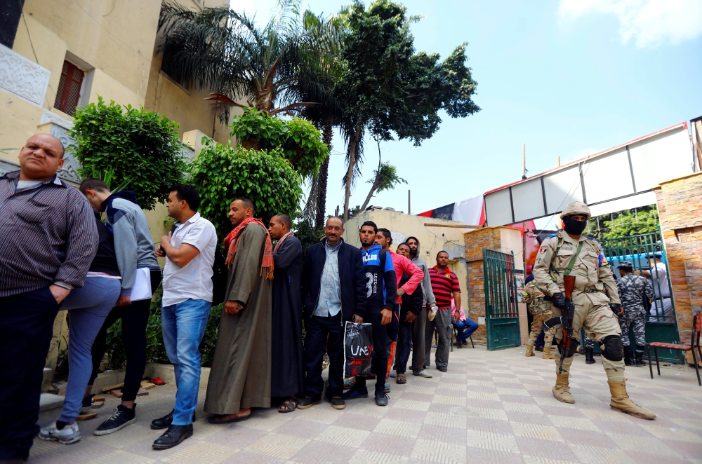 A soldier stands guard as people wait in line to cast their votes during the second day of the referendum on draft constitutional amendments, at a polling station in Cairo, Sunday. — Reuters