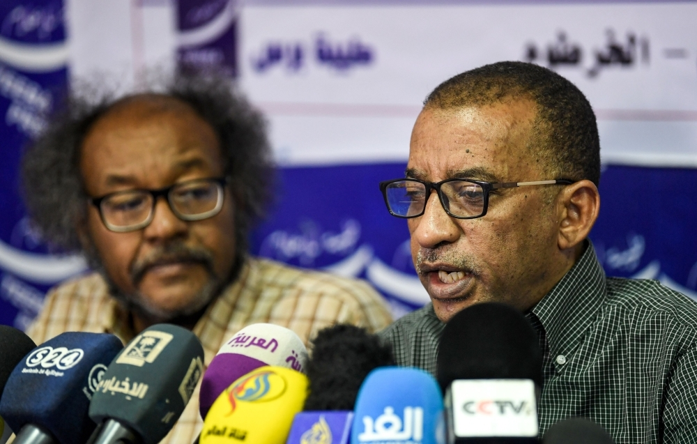 Sudanese civil society activists Muawia Shaddad, left, and Omar El-Digeir, right, two of the leaders from the protest movement led by the Alliance for Freedom and Change, give a press conference in the capital Khartoum on Wednesday. — AFP