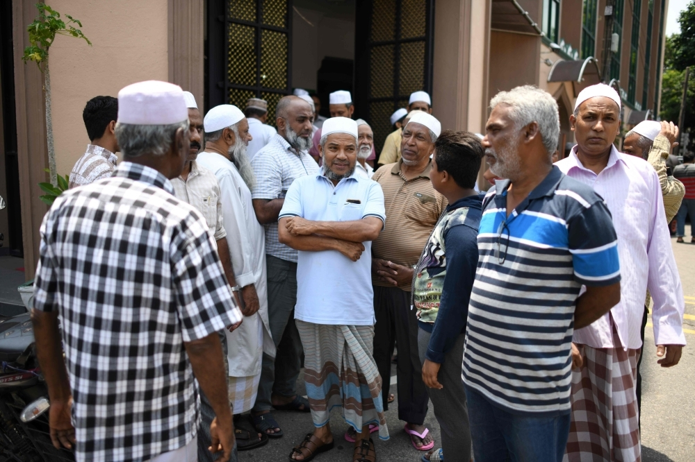 Members of the Sri Lanka Muslim community gather outside a mosque after prayers in Colombo on Tuesday. — AFP