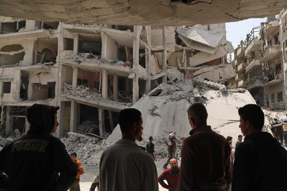 People watch as members of the Syrian Civil Defense search the rubble of a collapsed building following an explosion in the town of Jisr Al-Shughur, in the west of the mostly rebel-held Syrian province of Idlib, on Wednesday. — AFP