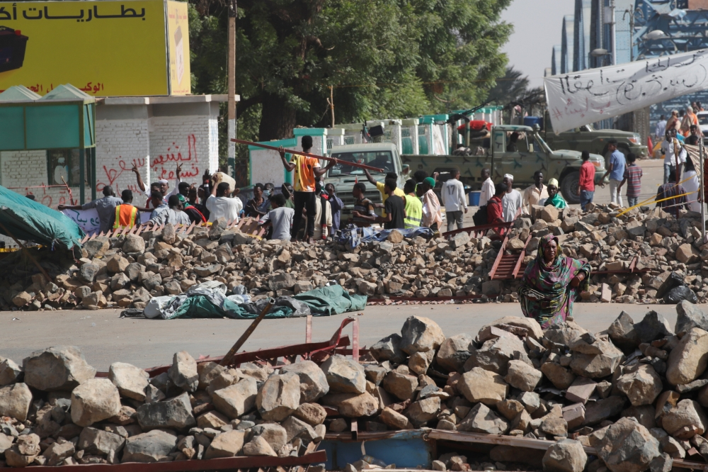 Sudanese protesters walk between barricades on a road leading to the defense ministry compound in Khartoum on Tuesday. — Reuters
