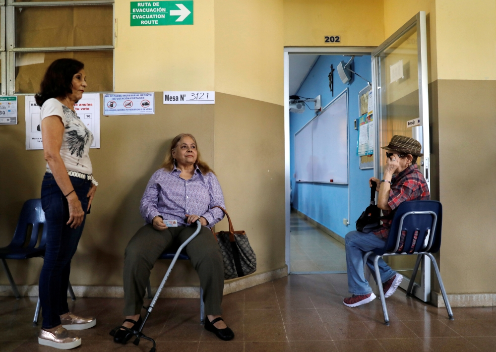 Voters wait for the polls to open to cast their ballots during the general election in Panama City, Sunday. — Reuters