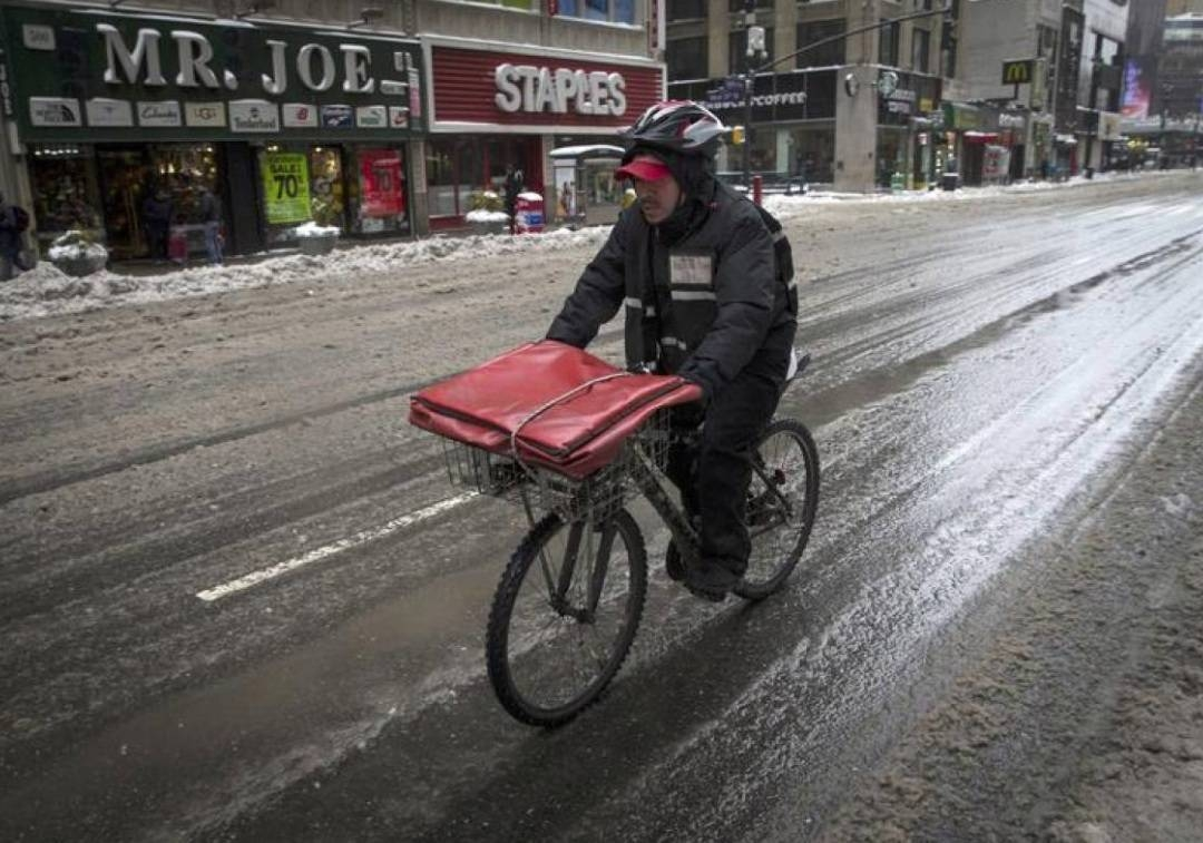 A pizza delivery man rides on a bicycle on 8th avenue in New York city as the city slowly returned to normal after being hit by winter storm Juno in this file photo. – Reuters