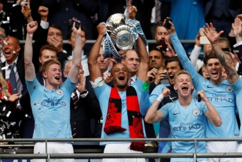 Manchester City's Vincent Kompany lifts the trophy as they celebrate after winning the FA Cup at Wembley Stadium in London on Saturday. — Reuters