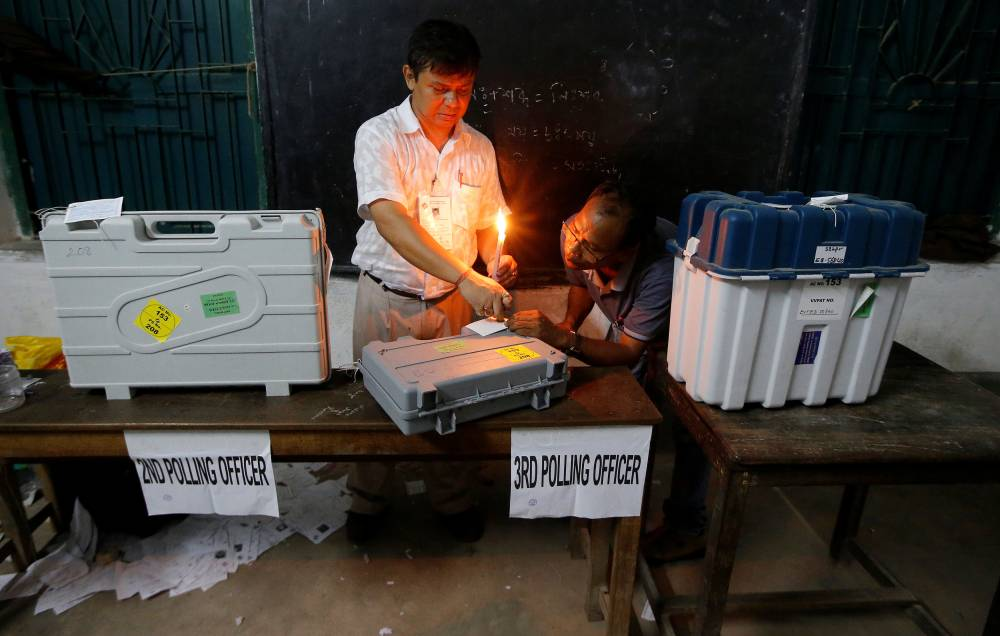 Polling officials seal an Electronic Voting Machine (EVM) and a Voter Verifiable Paper Audit Trail (VVPAT) machine at a polling station after the end of the last phase of the general election in Kolkata, India, Sunday. — Reuters