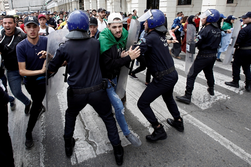 Students and police confront each other during an anti government protest in Algiers. — Reuters