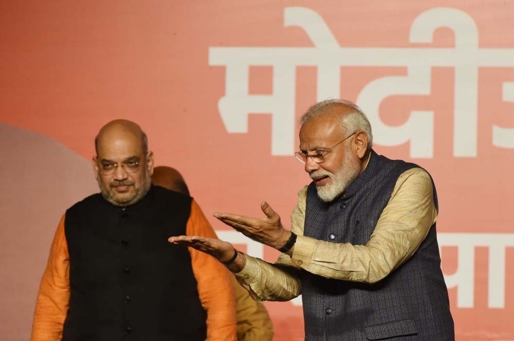 India Prime Minister Narendra Modi (R) gestures to supporters next to Bharatiya Janta Party (BJP) president Amit Shah wave as they celebrate the victory in India's general election at the party headquarters in New Delhi on Thursday. — AFP