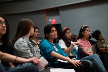 High school student poets listen to a poem about climate change in the New School auditorium as they prepare for final auditions for