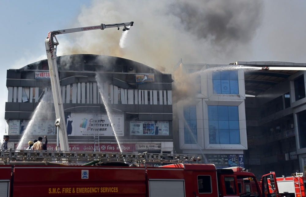 Firefighters douse a fire that broke out in a four-story commercial building in Surat, in the western state of Gujarat, India, on Friday. — Reuters