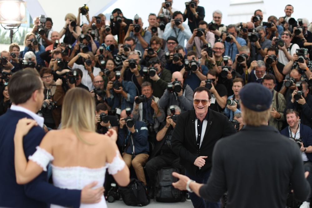 US film director Quentin Tarantino (2nd R) jokes with photographers while posing with US actor Leonardo DiCaprio (L), Australian actress Margot Robbie (2ndL) and US actor Brad Pitt during a photocall for the film
