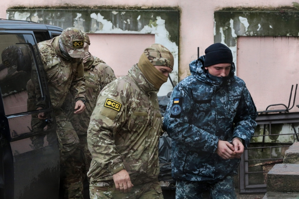 A Russia's FSB security service officer escorts a detained Ukrainian sailor to a courthouse in Simferopol, Crimea, in this Nov. 27, 2018 file photo. — AFP