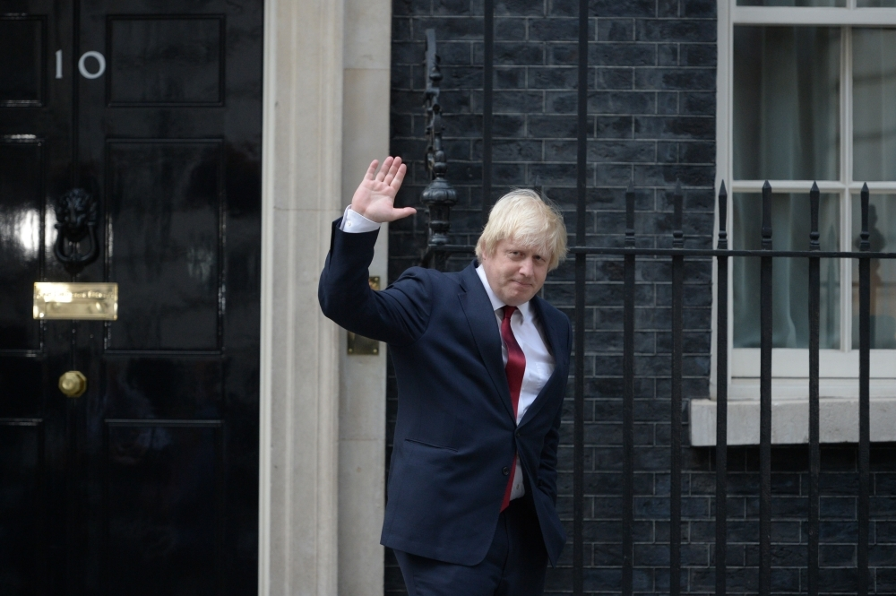 Newly appointed Foreign Secretary Boris Johnson waves as he leaves 10 Downing Street in central London on July 13, 2016 . - AFP