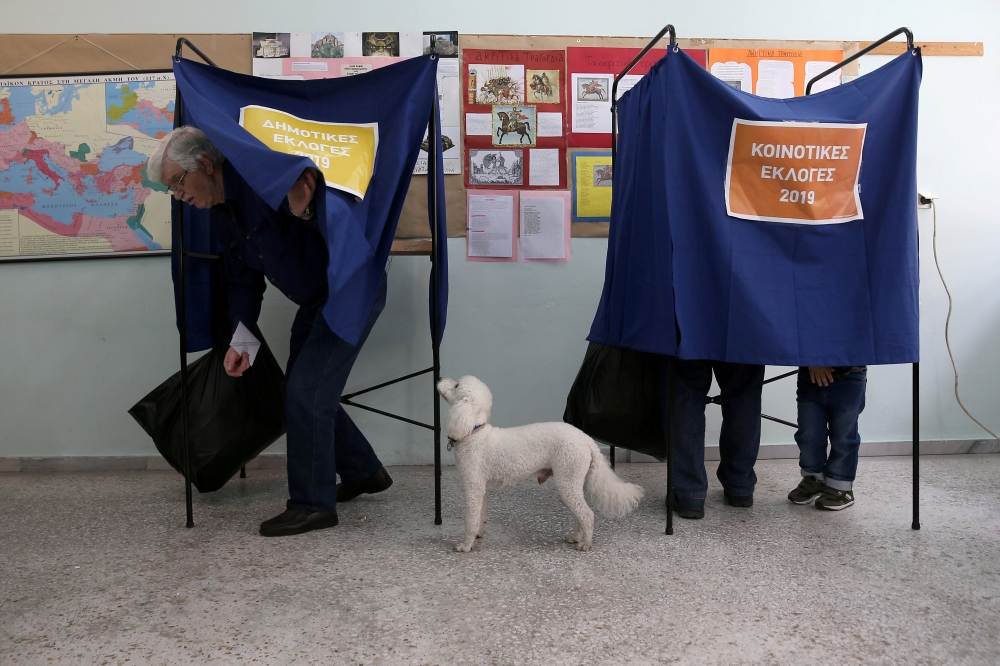 A dog stands next to its owner as he exits the polling booth, during the European Parliament and local elections at a polling station in Athens, Greece, Sunday. — Reuters