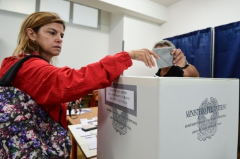 A woman casts her vote for the European elections at a polling station in southern Milan on May 26. - AFP