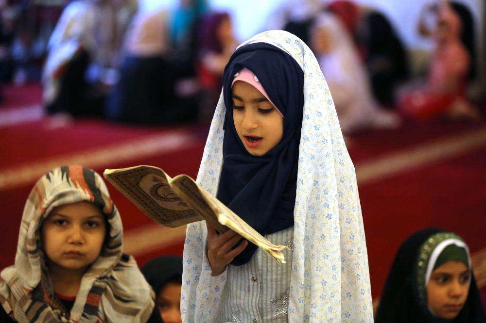 The blessed Qur'an  Iraqi children read the Holy Qur'an in Baghdad during the holy month of Ramadan.  — AFP
