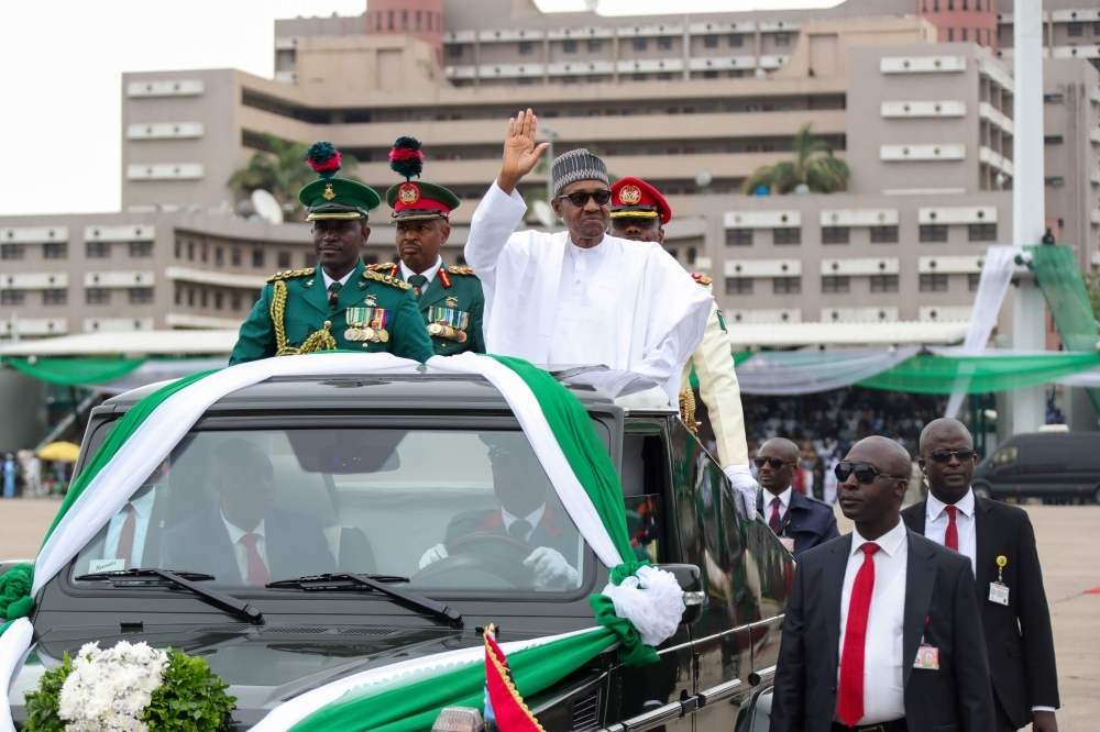 A handout image released by the Nigerian Presidential Press Services on Wednesday shows Nigerian President Muhammadu Buhari waving from a car as he arrives to his inauguration ceremony in Abuja. — AFP