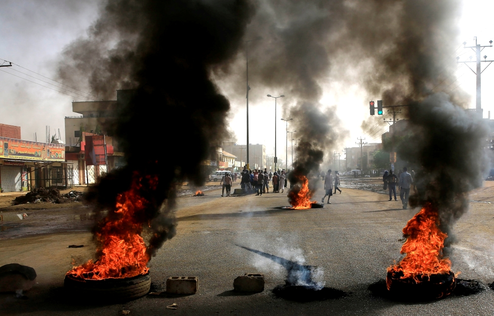 Sudanese protesters use burning tires to erect a barricade on a street in Khartoum on Monday. — Reuters