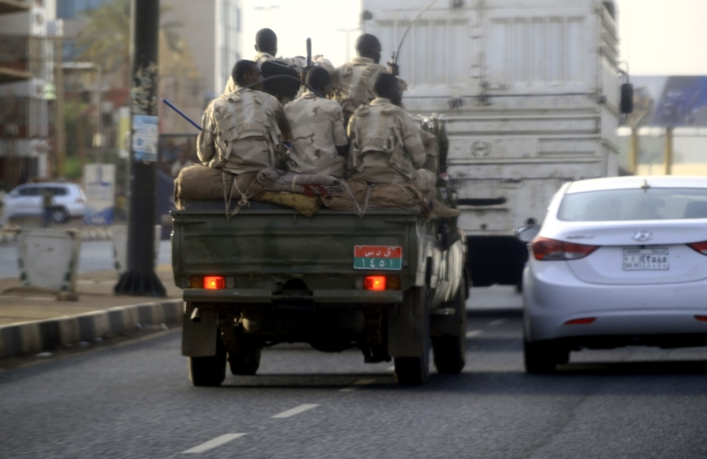 Sudanese security forces ride in the back of a pick up truck through a main avenue in Khartoum on Tuesday. — AFP