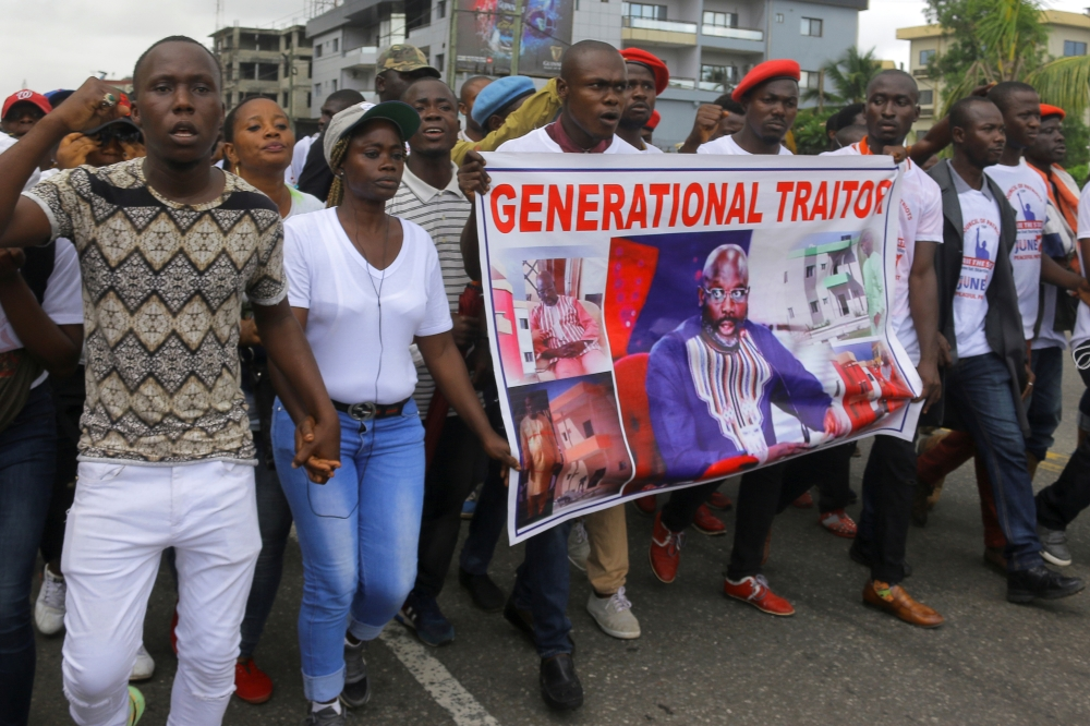 People carry a banner depicting Liberia's President George Weah as they march during a protest to voice discontent toward the presidency of Weah, whose policies they see as having failed to curb economic decline and mitigate corruption. — Reuters
