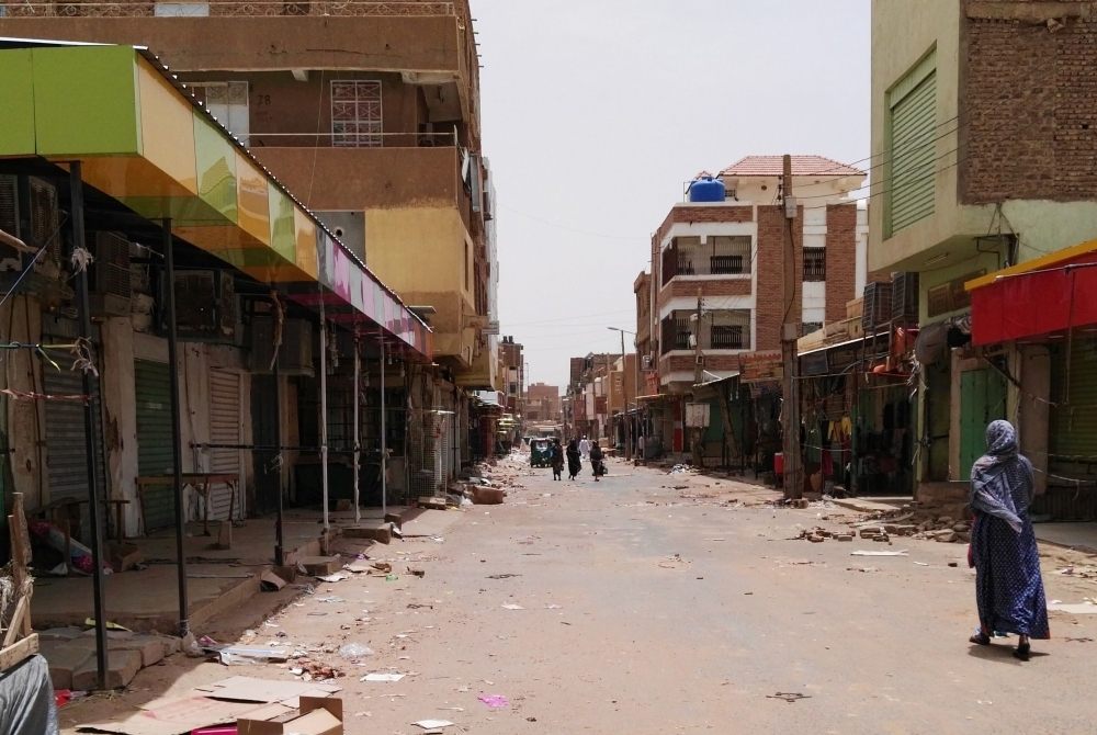 A Sudanese woman walks past closed shops in a commercial street in Khartoum's twin city Omdurman on the first day of a civil disobedience campaign across Sudan on Sunday. — AFP