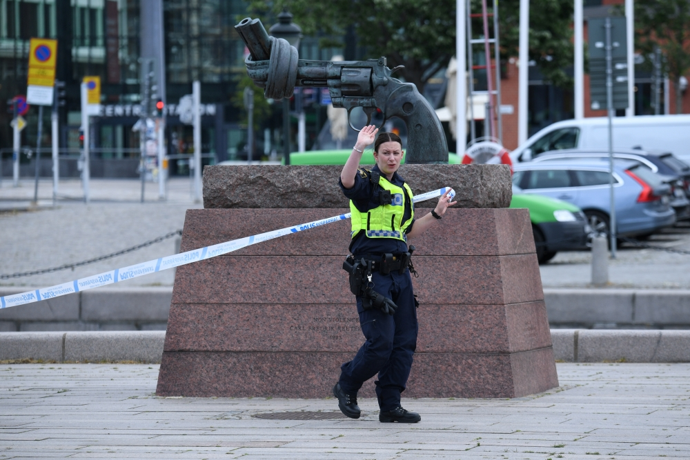 A police member gestures at Malmo central station after police shot a man for