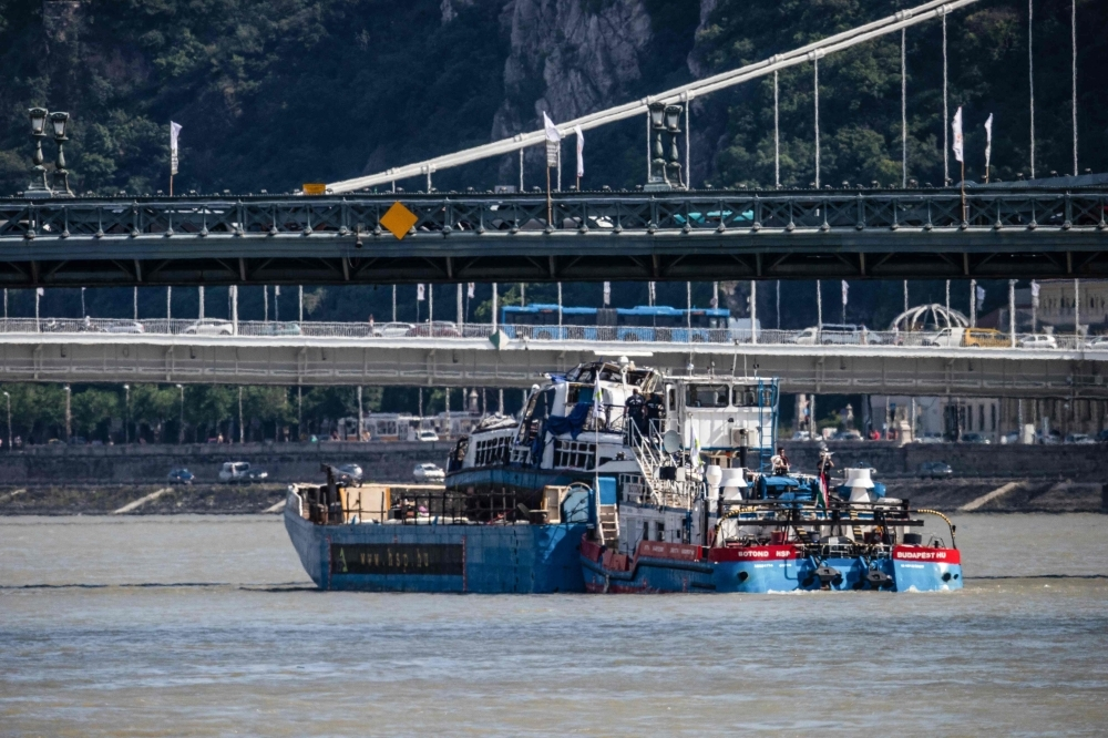 The recovered sunken Mermaid sightseeing boat is transported off the river Danube where it collided with a vessel in Budapest on Tuesday. — AFP