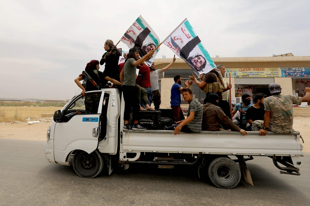 A convoy of Syrians follow the truck carrying the coffin of late rebel fighter Abdel-Basset Aal-Sarout on June 9, 2019, near the Bab Al-Hawa crossing point, northwestern Syria, on the way to his funeral after crossing the border from Turkey where he was receiving treatment following his injury earlier this week. — AFP