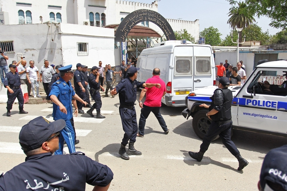 A Protester is pushed back by policemen as Algeria's former prime minister Abdelmalek Sellal is driven to custody at the El Harrach prison in the suburbs of the capital Algiers, on Thursday. Sellal was remanded in custody after appearing before a judge as part of an anti-corruption investigation, state media reported. — AFP