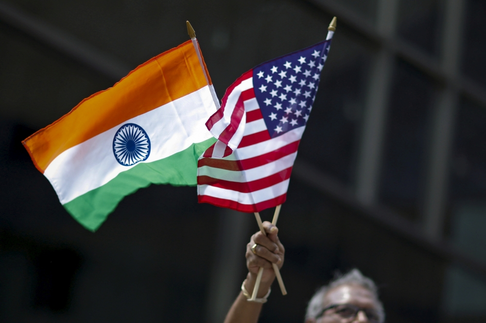 A man holds the flags of India and the US while people take part in the 35th India Day Parade in New York in this August 16, 2015, file photo. — Reuters