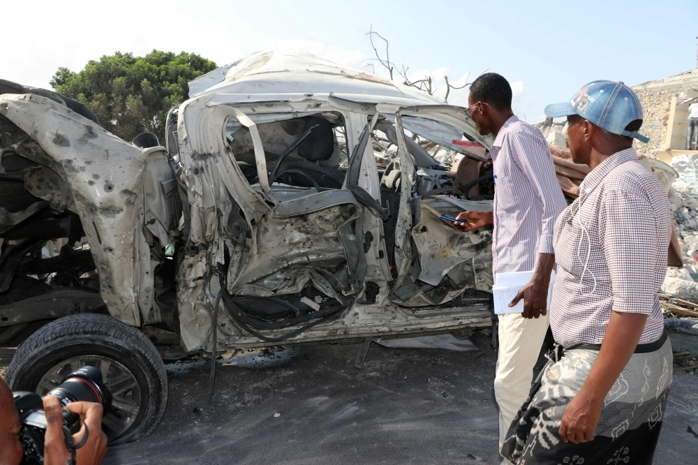 People looks at a destroyed car on the site of the explosion near the Somali parliament in the capital Mogadishu on Saturday. — AFP