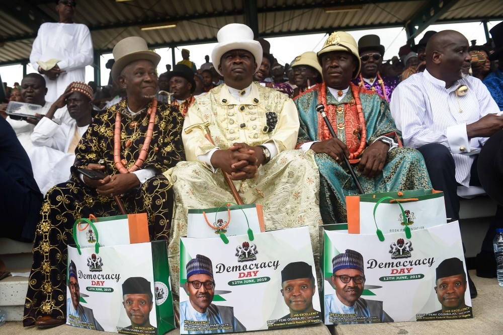 People wearing traditional costumes display gift bags with the pictures of the Nigerian President Muhammadu Buhari and Vice President Yemi Osinbajo during the Democracy Day celebrations in Abuja. — AFP
