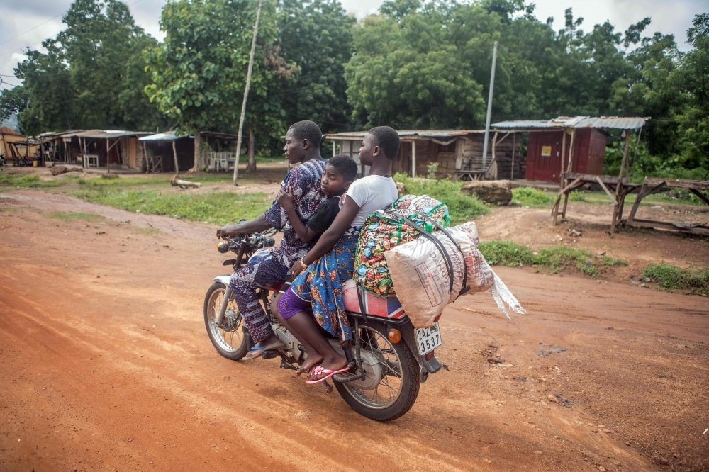 A family ride a motorbike as they flee the city of Save on Saturday following days of unrest in the West African country of Benin. — AFP