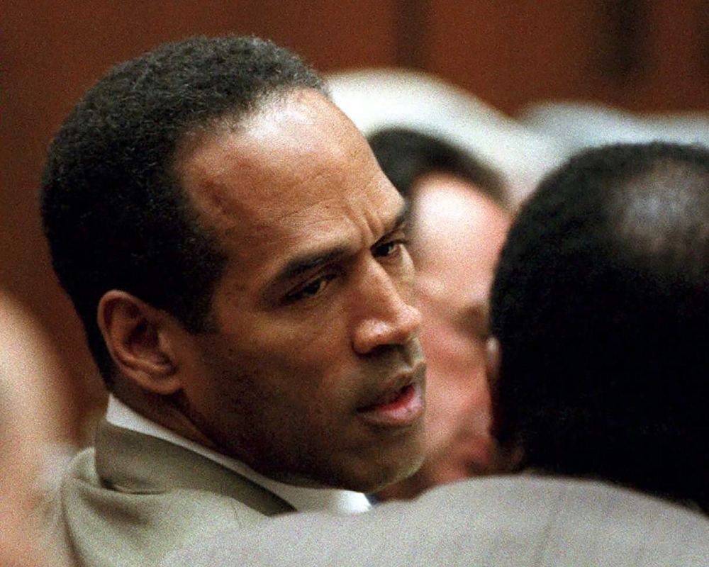 Double murder defendant O.J. Simpson, left, talks to attorney Johnnie Cochran Jr., during testimony by a Los Angeles Detective Ron Phillips in this Feb. 15, 1995 file photo. — AFP
