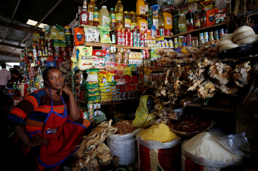 A woman sits near food items displayed for sale at a market in Abuja, Nigeria. — Reuters
