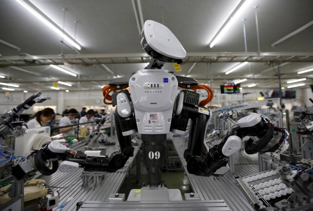 A humanoid robot works side by side with employees in the assembly line at a factory of Glory Ltd., a manufacturer of automatic change dispensers, in Kazo, north of Tokyo, Japan. — Reuters