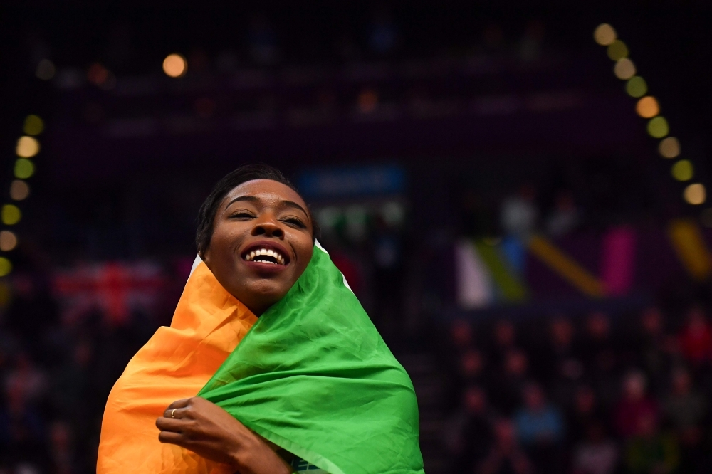 In this file photo taken on March 2, 2018, Gold medalist Ivory Coast's Murielle Ahoure wraps herself in the Ivorian flag as she celebrates after the women's 60m final event at the 2018 IAAF World Indoor Athletics Championships at the Arena in Birmingham. — AFP