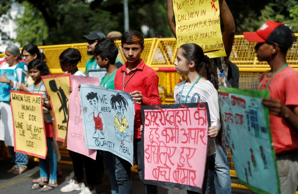 Children hold placards during a protest against the deaths of children who have died this month from encephalitis, commonly known as brain fever, in the eastern Indian state of Bihar, in New Delhi, on Monday. — Reuters