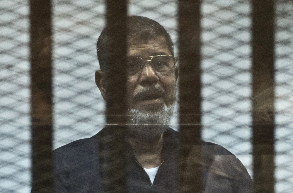 Egypt's former President Mohamed Morsi stands behind the bars during his trial in Cairo in this June 16, 2015 file photo. — AFP