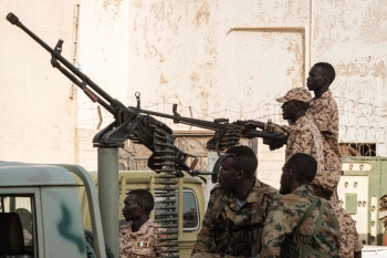 A member of Sudan's Rapid Support Forces (RSF) paramilitaries mans a machine gun turret while on guard outside the offices of the anti-corruption prosecution in the capital Khartoum. — AFP