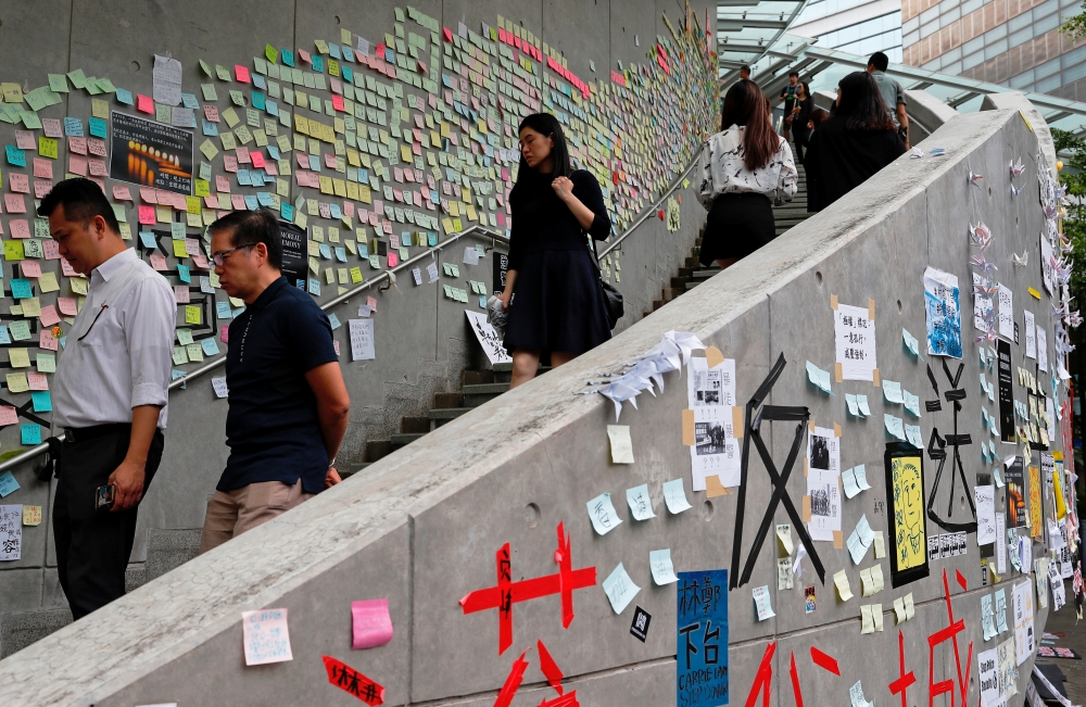 People walk past notes and placards with messages of support for the protest against the extradition bill, put on walls along a road near the Legislative Council building in Hong Kong, Tuesday. — Reuters
