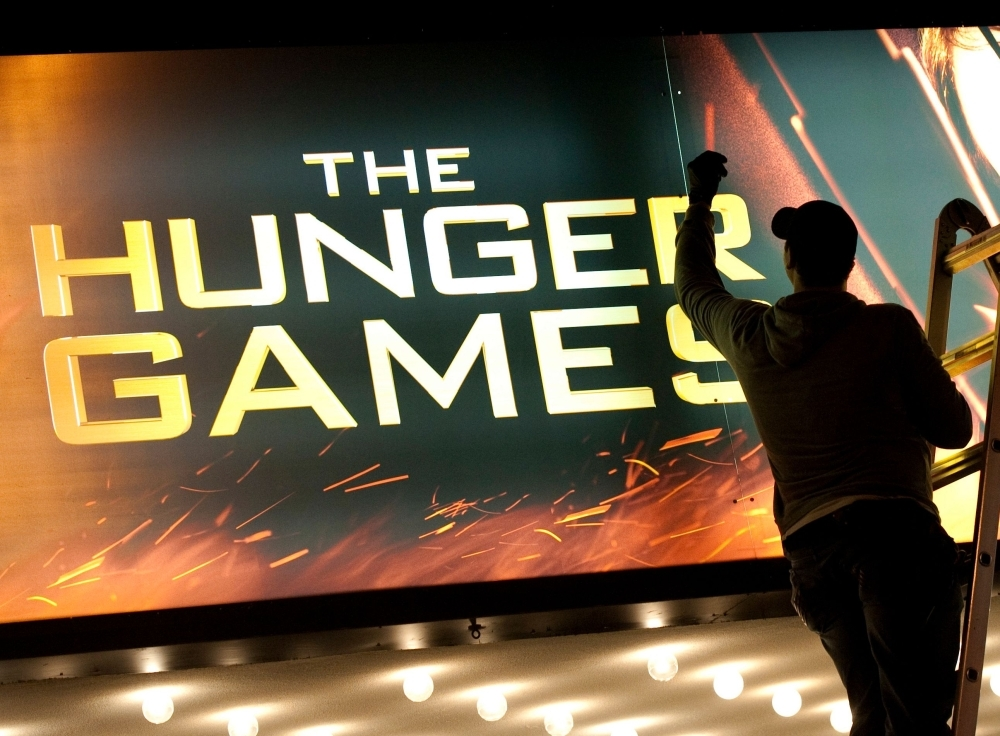 In this file photo taken on March 22, 2012 A worker swaps out the billboard marking the opening of  'The Hunger Games