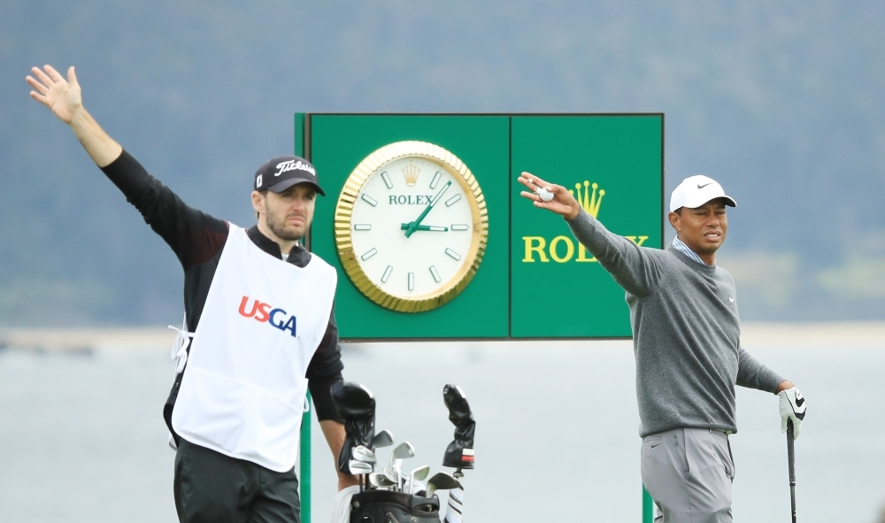 Tiger Woods of the United States reacts to his shot from the 18th tee as caddie for Byeong-Hun An of Korea, Daniel Parratt, looks on during the third round of the 2019 US Open at Pebble Beach Golf Links on Saturday in Pebble Beach, California. — AFP