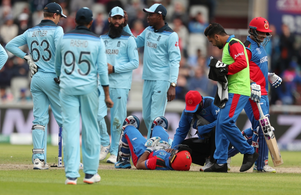 Afghanistan's Hashmatullah Shahidi is checked on by a physio after being hit on the head off a bowl from England's Mark Wood during the ICC Cricket World Cup match at the Old Trafford, Manchester, Britain, on Tuesday. — Reuters