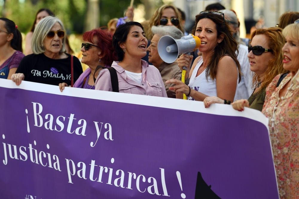 A group of women hold a banner reading