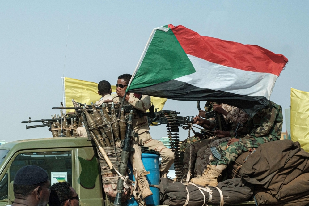 Members of the Rapid Support Forces (RSF) ride on an armed vehicle with the Sudanese national flag, in the capital Khartoum, Friday. — AFP