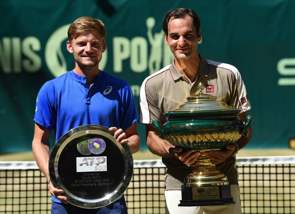 Roger Federer (R, 1st) from Switzerland and David Goffin (2nd) from Belgium pose with their trophies after their final match at the ATP tennis tournament in Halle, western Germany, on Sunday. — AFP