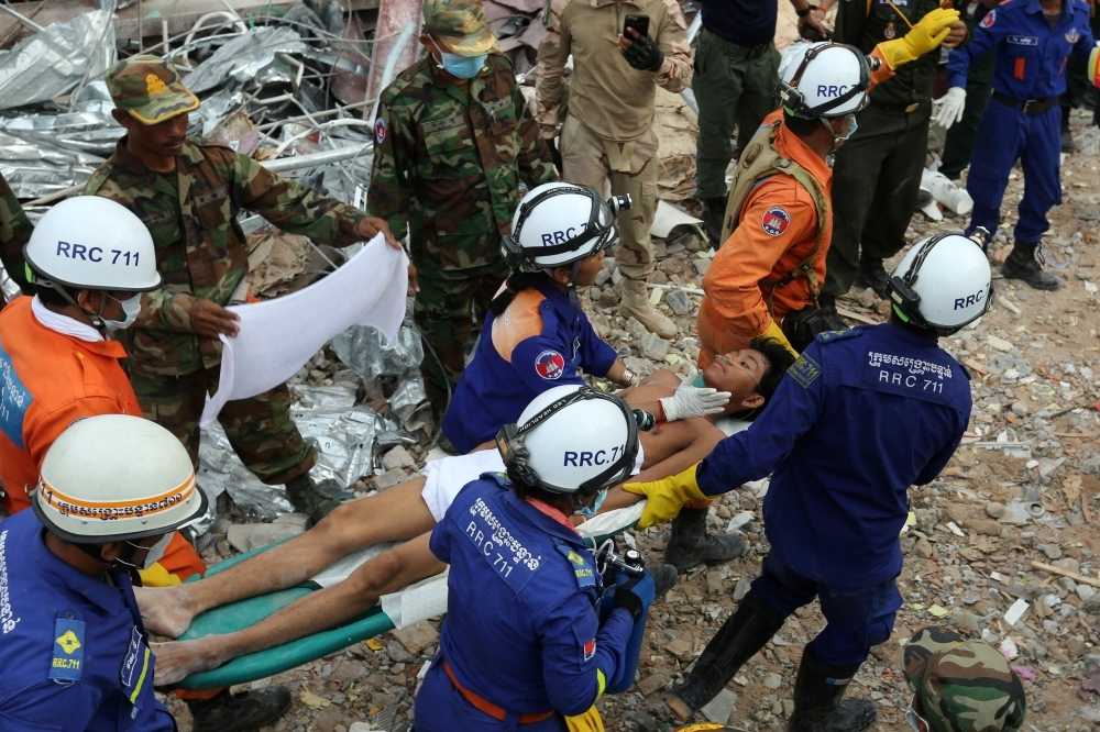 A survivor is carried out of the rubble from a collapsed building in Sihanoukville, Cambodia, on Monday. — AFP