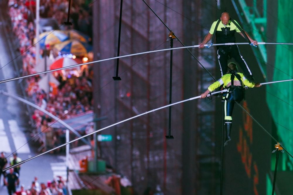Aerialist Nik Wallenda walks the highwire with his sister Lijana as they greet the crowd over Times Square in New York. — Reuters