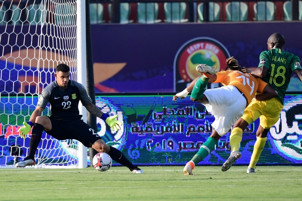 Ivory Coast's forward Jonathan Kodjia (2nd-R) scores a goal in front of South Africa's goalkeeper Rowen Williams during the 2019 Africa Cup of Nations (CAN) football match against South Africa at the Al Salam Stadium in Cairo on Monday.  — AFP