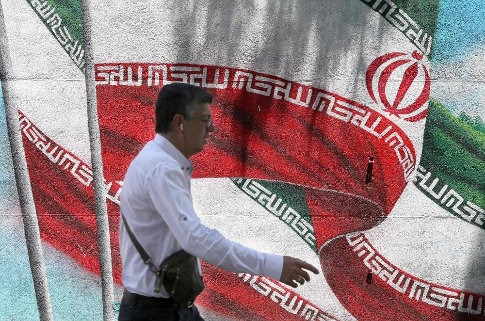 An Iranian man walks past a mural painted with the Iranian flag in Tehran. — AFP